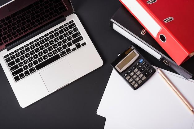 Widok z góry laptopa; foldery z plikami; kalkulator; ołówki i papier na czarnym tle