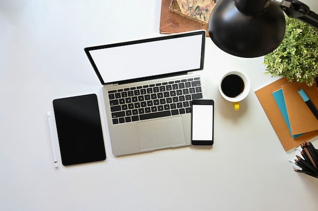Widok z góry laptopa komputerowego z białym pustym ekranem składającym się z czarną tabletką z pustym ekranem, białym smartfonem z pustym ekranem, notatnikiem, rośliną doniczkową, lampą, uchwytem na filiżankę i książkami.