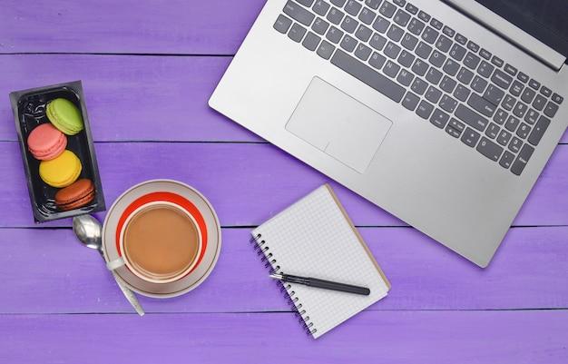 Widok z góry laptopa, makaroniki i filiżankę kawy z notatnikiem