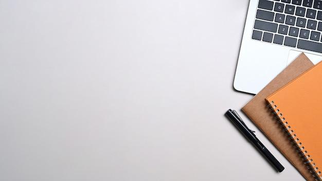 Widok z góry laptopa, notebooka i pióra na białym stole.