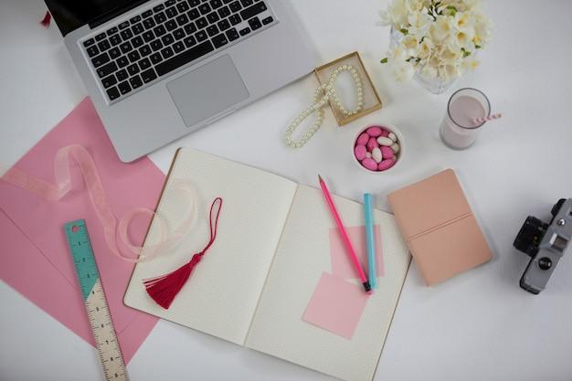 Widok z góry laptopa, pamiętnik, karteczki, aparat i ołówek