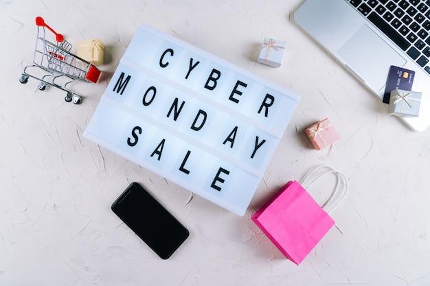 Widok z góry laptopa, słowa sprzedaży promocji w cyber poniedziałek na lightbox, pudełka na prezenty, laptop, zakupy