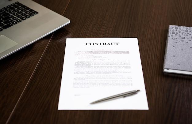 Widok z góry laptopa, umowy, terminarza i pióra na drewnianym stole w biurze.