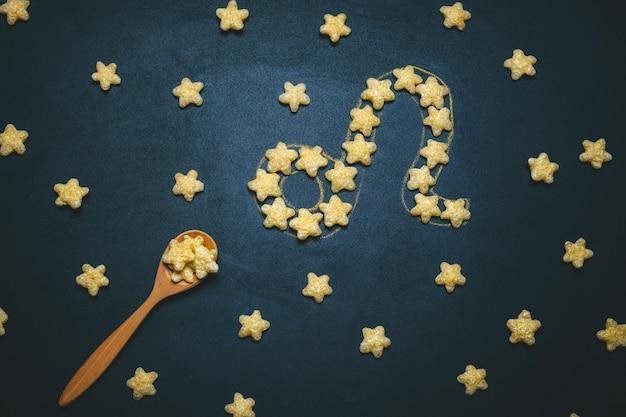 Widok z góry leżał znak horoskopu leo wykonany z chrupiących gwiazd kukurydzy na czarnym tle