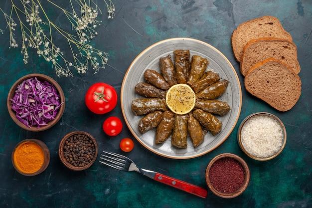Widok z góry liść dolma pyszny wschodni posiłek mięsny zawinięty w zielone liście z pomidorami i chlebem na niebieskim biurku mięso jedzenie obiad danie zdrowie warzyw