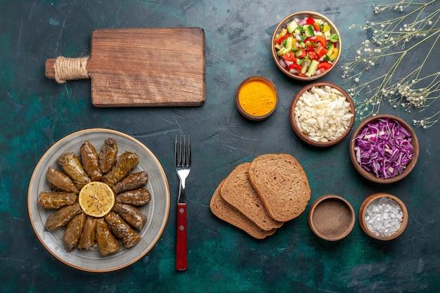 Widok z góry liść dolma wschodni posiłek mięsny zawinięty w zielone liście z pokrojonymi warzywami i chlebem na niebieskim biurku danie mięsne wschodni posiłek