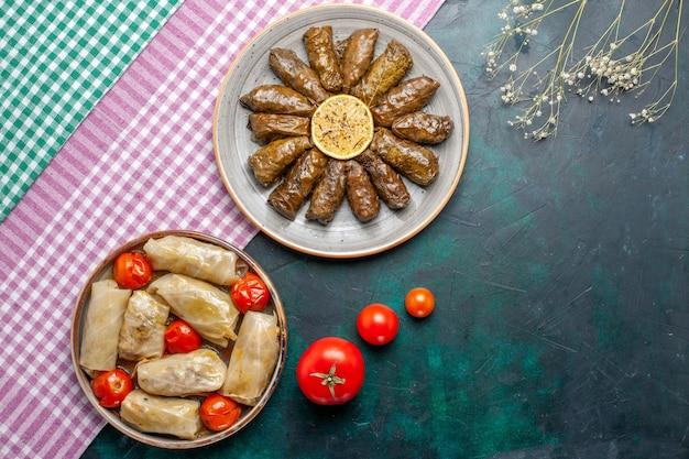 Widok z góry liść dolma wschodnia mączka mięsna zawijana wewnątrz zielonych liści z kapustą dolma na niebieskim biurku mięso danie obiadowe wschodni posiłek kalorie