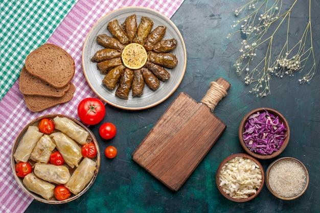 Widok z góry liść dolmy wschodnia mączka mięsna zawinięta w zielone liście z chlebem i kapustą dolma na ciemnoniebieskim biurku mięsne danie obiadowe wschodni posiłek