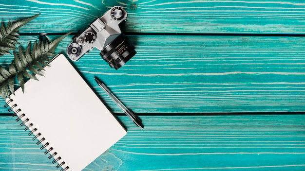 Widok z góry liści paproci; aparat fotograficzny; spiralny notatnik i długopis na turkusowym tle drewnianych