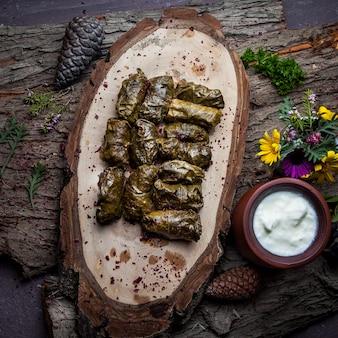 Widok z góry liście winogron dolma faszerowane mięsem i ryżem z sosem śmietanowym. tradycyjna kuchnia wschodnioeuropejska i azjatycka