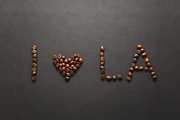 Widok z góry listu i love los angeles - serca la słowa wykonane z ziaren kawy na czarnym tle do projektowania