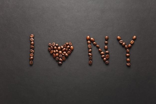 Widok z góry listu i love new york - serce ny słowa wykonane z ziaren kawy na czarnym tle do projektowania