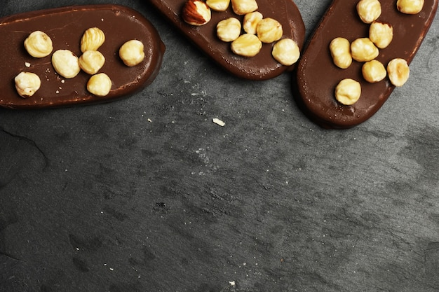 Widok z góry lodów czekoladowych na ciemnym tle łupków z płaskimi orzechami laskowymi