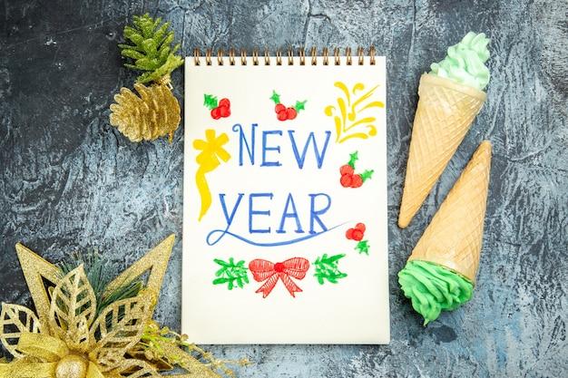 Widok z góry lody nowy rok napisany na notebooku ozdoby świąteczne na szarym tle