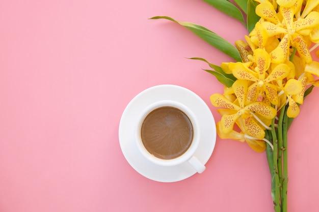 Widok z góry lub na płasko leżały żółte kwiaty orchidei i filiżanka kawy na różowo.