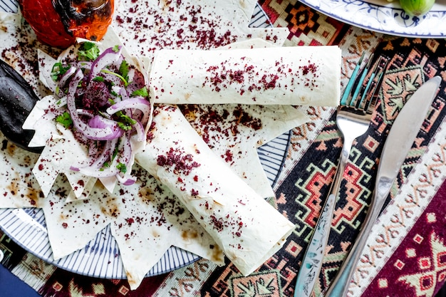 Widok z góry lula kebab w chlebie pita z warzywami i cebulą posypaną sumakiem
