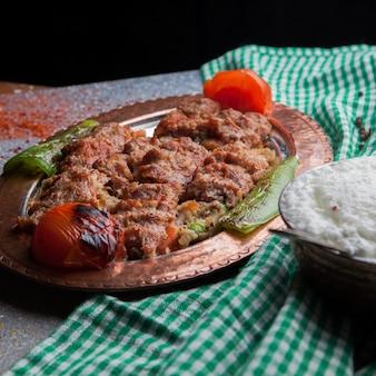 Widok z góry lule kebab pod sałatką z bakłażana z pomidorem, papierem i ajranem