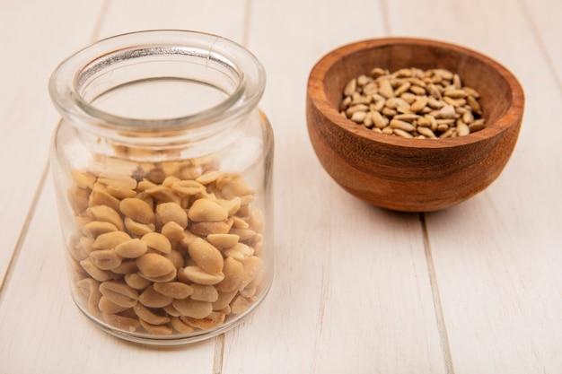 Widok z góry łuskanych nasion słonecznika na drewnianej misce z orzeszkami pinii na szklanym słoju na beżowym drewnianym stole