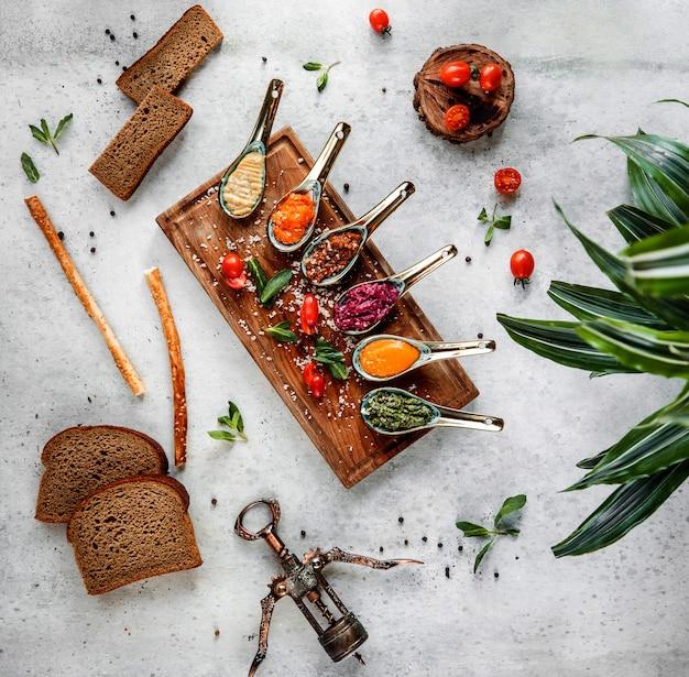 Widok z góry łyżek różnych sosów na szaro