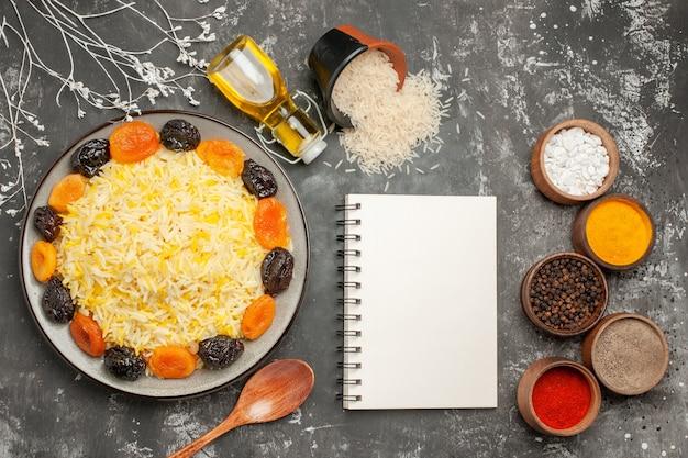 Widok z góry łyżka do ryżu butelka oleju talerz ryżu z suszonymi owocami przyprawy ryż biały notatnik