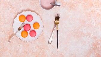 Widok z góry macaroons na białym talerzu ceramicznym z widelcami na teksturowanej tle