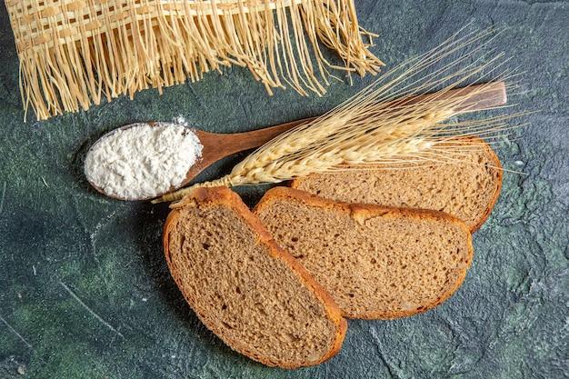 Widok z góry mąka na drewnianą łyżkę z ciemnymi bochenkami chleba na ciemnym biurku