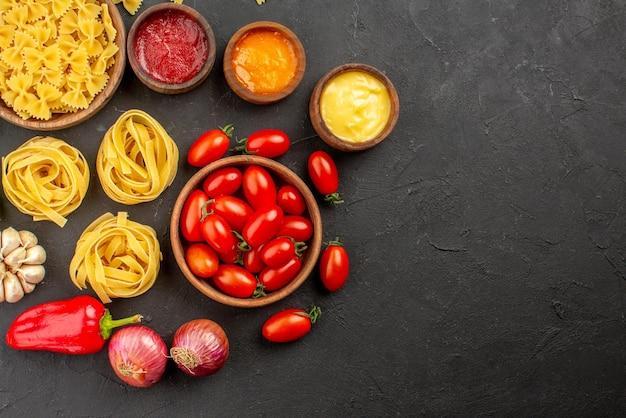 Widok z góry makaron i pomidory miski makaronu i pomidorów cebula czosnek trzy rodzaje sosów na stole