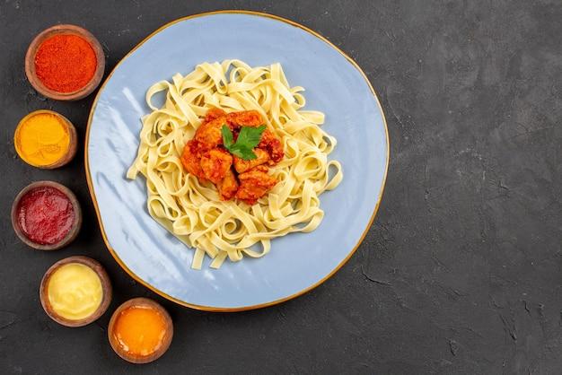 Widok z góry makaron i sosy sos makaronowy i apetyczne mięso na talerzu oraz sześć rodzajów różnych kolorowych sosów na stole