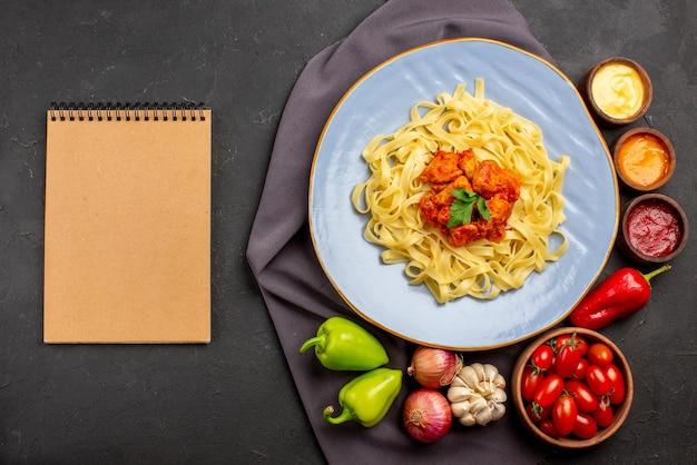 Widok z góry makaron na obrusie niebieski talerz apetycznego makaronu miska pomidorów sosy czosnek cebula papryka na fioletowym obrusie i kremowy notatnik na stole
