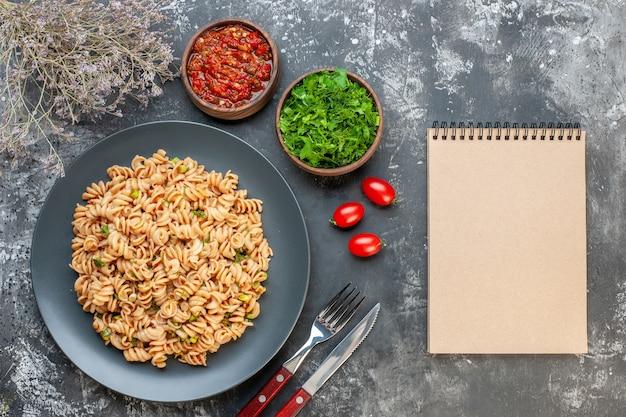 Widok z góry makaron rotini na okrągłym talerzu sos pomidorowy posiekana natka pietruszki w małych miseczkach pomidory wiśniowe widelec i nóż notatnik na ciemnym stole