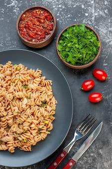 Widok z góry makaron rotini na szarym talerzu sos pomidorowy posiekana natka pietruszki w małych miseczkach pomidorki wiśniowe widelec i nóż na ciemnym stole