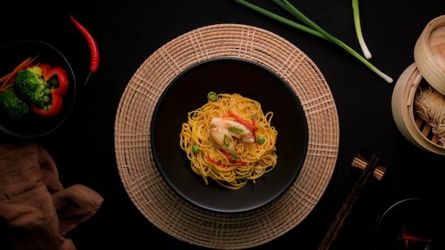 Widok z góry makaron schezwan lub chow mein z sosem warzywnym, kurczakiem i chili