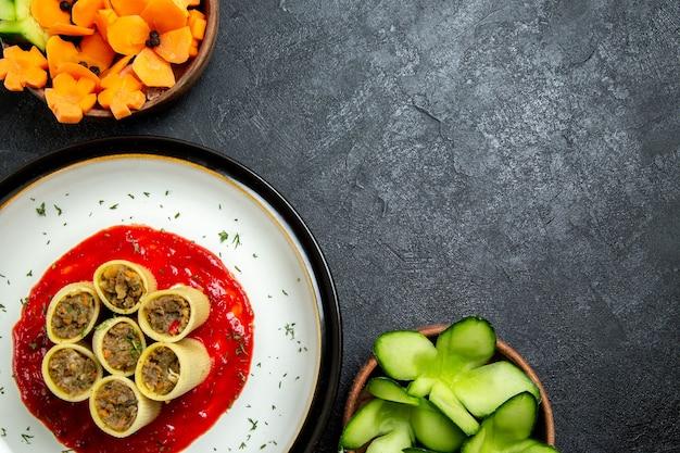 Widok z góry makaron z mięsem i sosem pomidorowym na szarym biurku ciasto makaronowe jedzenie