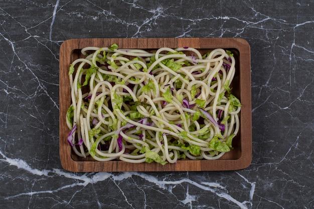 Widok z góry. makaron z sosem warzywnym w drewnianej misce.