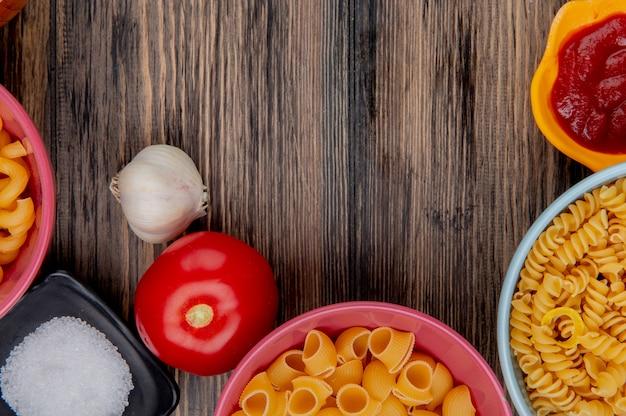 Widok z góry makaronów jako rotini pipe-rigate i innych w miseczkach z keczupem, solonym, czosnkowym pomidorem na drewnie