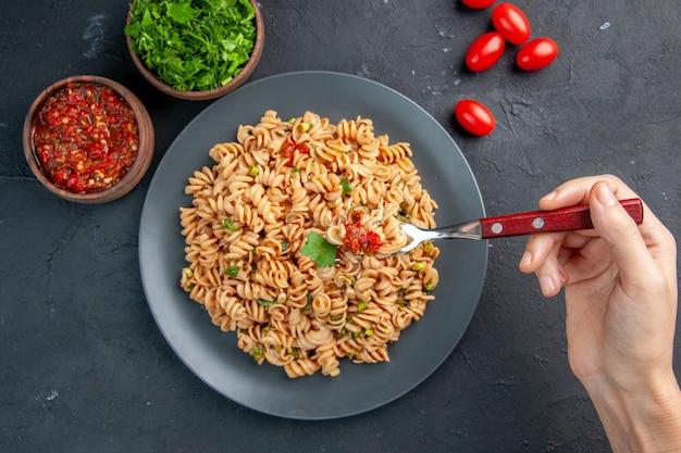 Widok z góry makaronu rotini na talerzu na widelcu w ręce kobiety z pomidorami koktajlowymi, sosem pomidorowym i posiekaną zieleniną w miseczkach na ciemnej odizolowanej powierzchni
