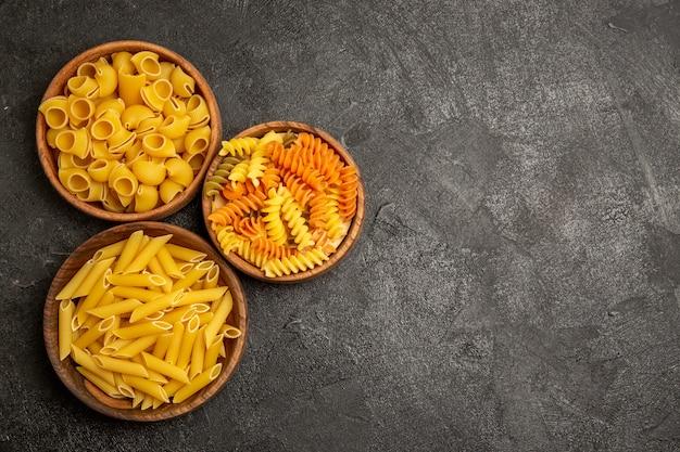 Widok z góry makaronu skład surowych produktów wewnątrz talerzy na szaro