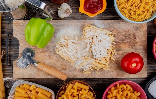 Widok z góry makaronu tagliatelle z mącznym pieprzem i pomidorem na desce do krojenia z innymi rodzajami soli keczupu czosnkowego na drewnianej powierzchni