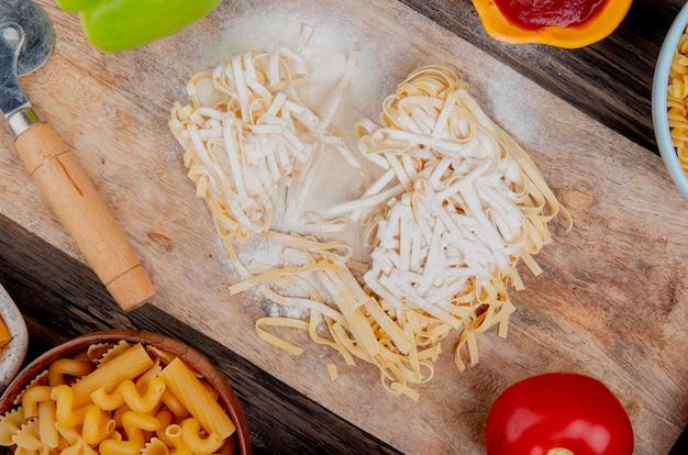 Widok z góry makaronu tagliatelle z pieprzem mąki i pomidorem na desce do krojenia z innymi rodzajami keczupu na powierzchni drewnianych