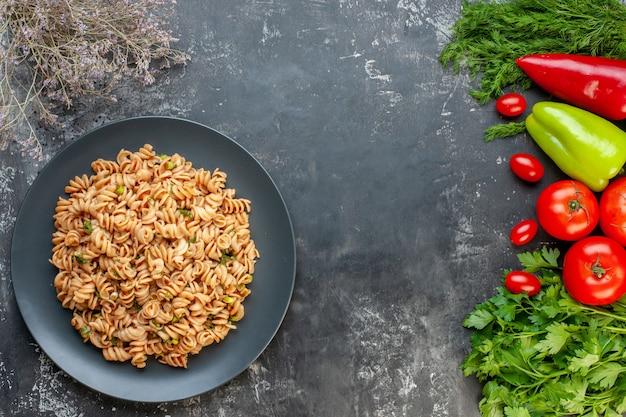 Widok z góry makarony rotini na okrągłym talerzu papryka pomidory pomidory pietruszka koper na szarym stole wolne miejsce
