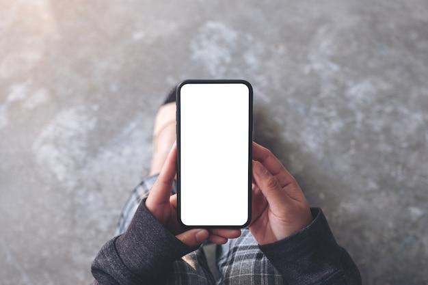 Widok z góry makieta obraz kobiety trzymającej czarny telefon komórkowy z pustym ekranem pulpitu siedząc na podłodze