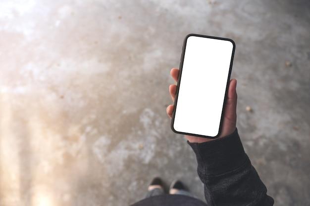 Widok z góry makieta obraz kobiety trzymającej czarny telefon komórkowy z pustym ekranem pulpitu, stojąc na betonowej podłodze