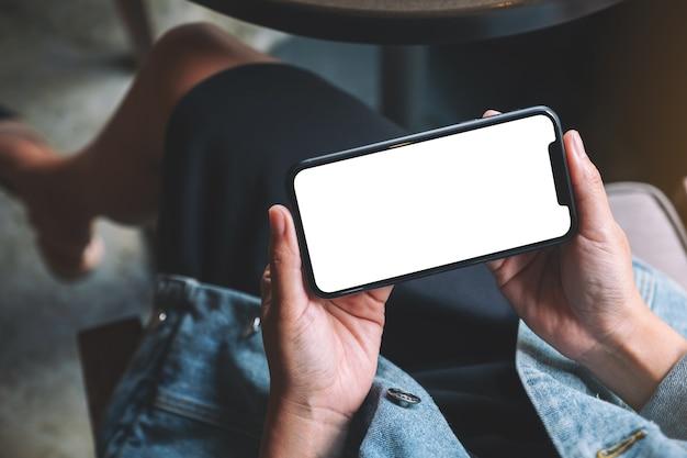 Widok z góry makieta obraz kobiety trzymającej czarny telefon komórkowy z pustym ekranem w kawiarni