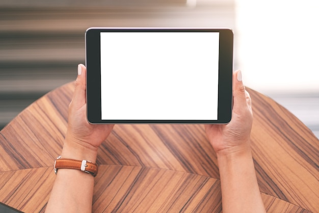 Widok z góry makieta obrazu kobiety siedzącej i trzymającej czarny tablet pc z pustym białym ekranem pulpitu na drewnianym stole