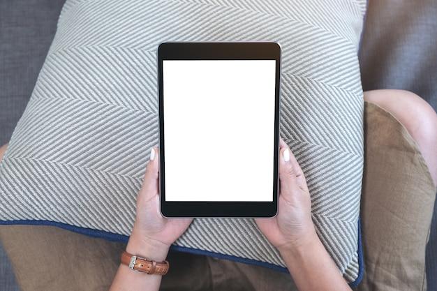 Widok z góry makieta obrazu kobiety trzymającej czarny tablet pc z pustym białym ekranem pulpitu, siedząc w salonie z uczuciem relaksu