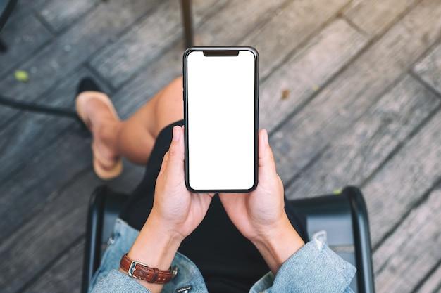 Widok z góry makieta obrazu kobiety trzymającej czarny telefon komórkowy z pustym białym ekranem pulpitu