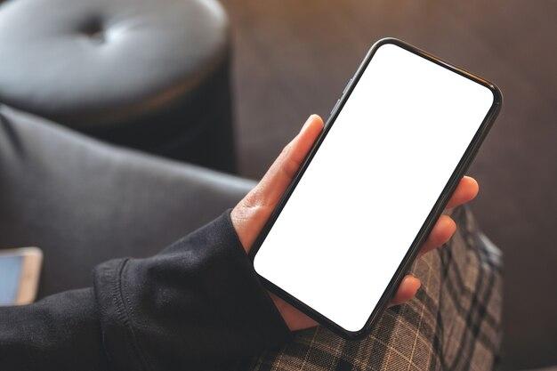 Widok z góry makieta obrazu rąk trzymających czarny telefon komórkowy z pustym białym ekranem w kawiarni