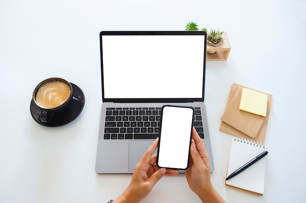 Widok z góry makieta obrazu rąk trzymających pusty biały ekran telefonu komórkowego i laptopa na stole w biurze