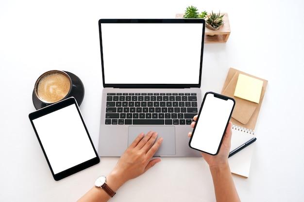 Widok z góry makieta obrazu rąk trzymających pusty biały ekran telefonu komórkowego z laptopa i komputera typu tablet na stole w biurze