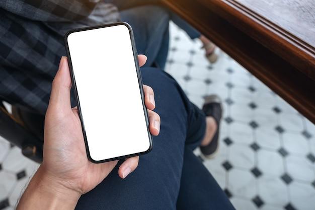 Widok z góry makieta obrazu ręki mężczyzny trzymającego biały telefon komórkowy z pustym ekranem pulpitu na udzie w kawiarni